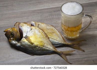 Beer mug and dried fish on wooden table.