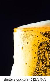 Beer mug with froth over black background