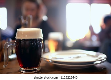 beer mug on a blurred background / beer restaurant beautiful dark beer in a mug in the interior of a pub