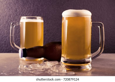 Beer in mug on concrete table near granite background.