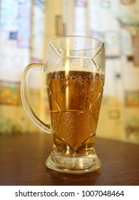 a beer mug on a dark table by the window