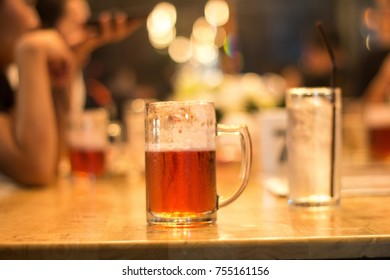 Beer mug on wood table in celebration, warm vintage restaurant