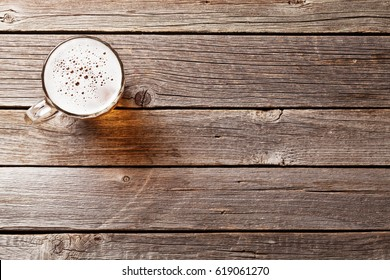 Beer mug on wooden table. Top view with copy space