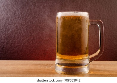 Beer in mug on wooden table near granite background.Free space for text.