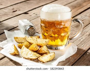 Beer mug and potato wedges on rustic vintage planked wood table - snack bar or pub menu