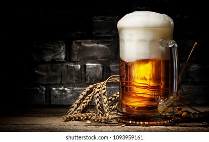 Beer in mug and wheet on wooden table and black background