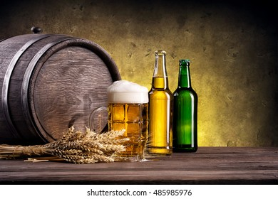 Beer mug with yellow and green bottle on a background of wooden barrels