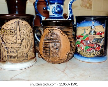 Beer mugs on the kitchen table. Ceramics Latvia and Hungary. Folk craft Latvia and Hungary. Traditionally, the products are painted with restrained, earthy shades. Selective focus.