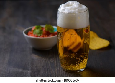 Beer with nachos and salsa in the background
