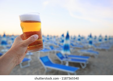 Beer on beach. Hand holding plastic glass of beer on beach background. Evening relaxation in Rimini, Italy.