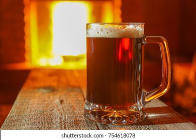 Beer on wooden table against fireplace background.