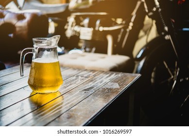 Beer on the wooden table with bigbike as background.