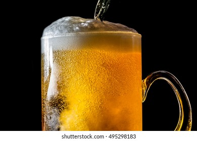 Beer overflowing large glass with foam and bubbles isolated on a black background