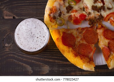 Beer and pizza on dark wooden background. Ale and food. View from above, top, horizontal