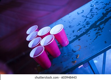 Beer Pong playing at a party, American red cups standing on a textured wet table night club