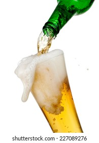 Beer pour and overflow in a glass from a green bottle