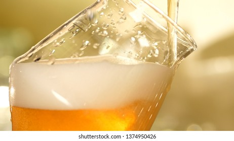 Beer is poured into a glass close-up on a blurred background