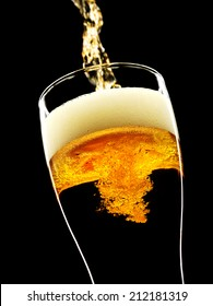 a beer pouring in a glass on a black background