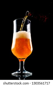 Beer is pouring into a glass from bottle isolated on black background