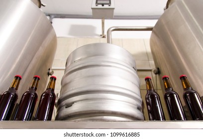 Beer production / micro brewery. Metal  barrel and beer bottles, bottom view
