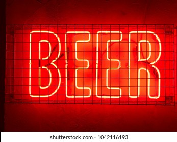 Beer red neon sign fixed to a wall behind metal cage