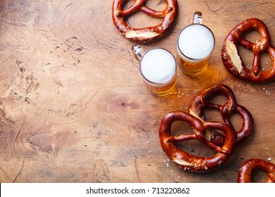 Beer, salted pretzels, potato chips on wooden background. Top view. Copy space.