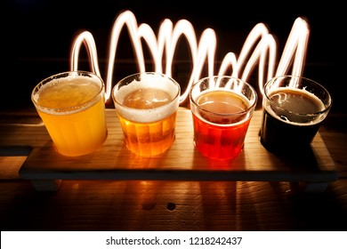 Beer samplers in small glasses individually placed in holes into a unique wooden tray and background. Amazing abstract colored lights in motion. Magical light in a glass of craft beer.
