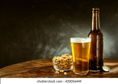 Beer served from a brown bottle into a long glass and a bowl of roasted salted peanuts on an old wooden bar table with copy space on slate behind