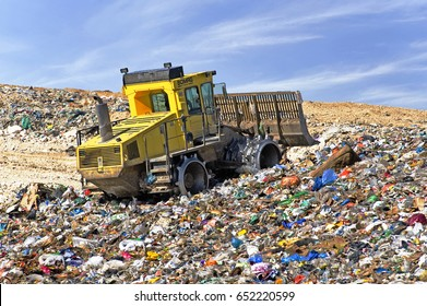 Beer Sheva, Israel, March 10 2012: Bulldozer compactor flattening garbage in a landfill waste site