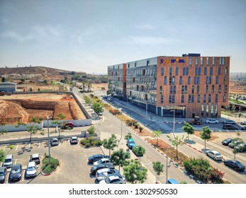 Beer Sheva, Israel-August 29, 2018: A view at Gav Yam Negev 3 building in the Advanced Technologies Park on the right and construction site excavated foundation pit separated with a fence on the left