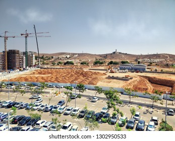 Beer Sheva, Israel-August 29, 2018: A huge public parking lot at front view and ground works in foundation pits in progress at the back view. Advanced Technologies Park is under construction.