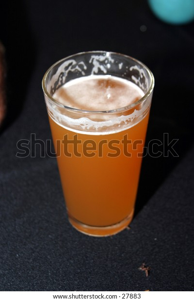 beer sitting in a glass after a sip or two so that the foamy head is now gone