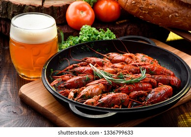 Beer Snack. Light beer in a transparent bobkale and Boiled crayfish in a cast-iron pan on a light wooden board on a dark wooden table, decorated with vegetables. Close-up. Space