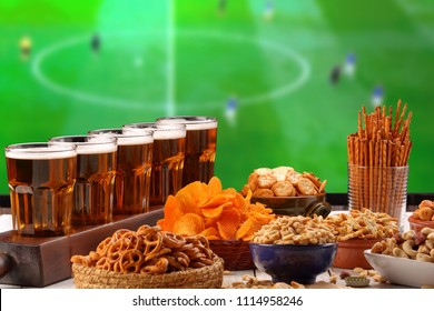 Beer and snack on football match field from tv background and empty space for text