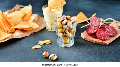 beer snacks at the bar: chips, nachos with sauce, pistachios and salami, aperitif, relax in the bar with friends, beer party.  selective focus and copy space
