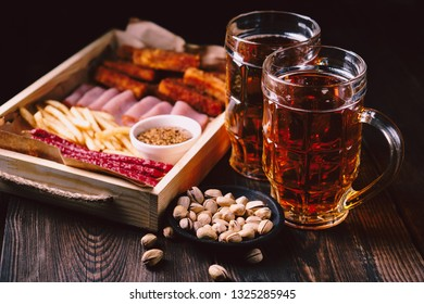 beer and snacks. bar table. restaurant, pub, oktoberfest food. delicious lager drink and appetizers set- fried cheese, ham, sausages and jerky. friday party atmosphere, craft brewery concept