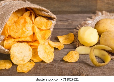 beer snacks potato chips and nuts in a sack on wooden background