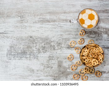 Beer with a soccer ball on a beer foam with pretzels. Top view. Space for text.