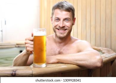 Beer spa. Handsome man enjoys bathing in logs with thermal water drinking beer mug.