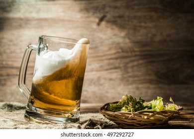 Beer spills from tankard on empty wooden background next to hop in basket