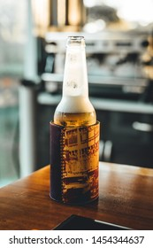 Beer in stubbie holder sits on wooden table of outdoor entertaining area.