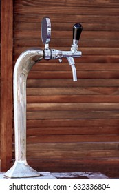 Beer tap chromeplated, against the background of a wooden wall.