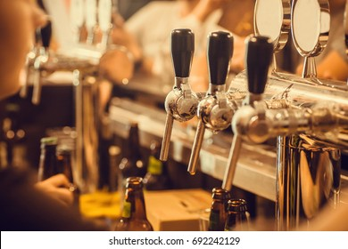 Beer tap with fresh brewed drink in busy pub in Europe.