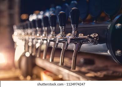 Beer tap in the row in beer bar