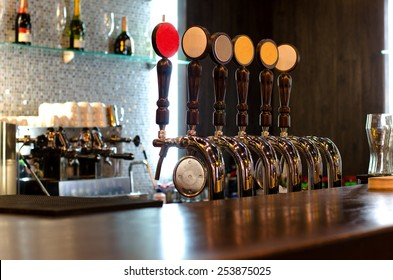 Beer taps behind a deserted bar counter for dispensing draft beer from a large storage keg below the wooden counter