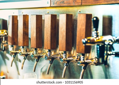 The beer taps in a pub. nobody. Selective focus. Alcohol concept. Vintage style. Beer craft. Bar table. Steel taps. Shiny taps.