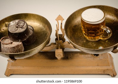 Beer and water on vintage scales, an alcoholism concept