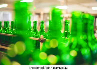Beer or wine bottles on the conveyor belt. Bottling alkoholic drink. Bottles filled with wine by an industrial machine in a winery factory.