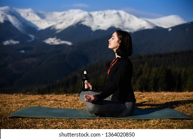 Beer yoga. Young woman doing yoga exercise in beautiful mountains