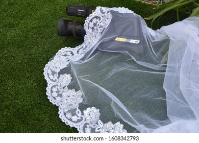 Beer-Sheva. Negev/Israel - November 2019 : a black large videographer's video camera lies on the green grass, near the white lace of a bride's wedding dress, blank, background, objects